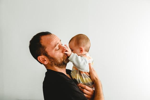 Boczny portret uroczy dziecko dotyka jego twarz w jego ojca rękach z jego małymi rękami, biały tło. Premium Zdjęcia