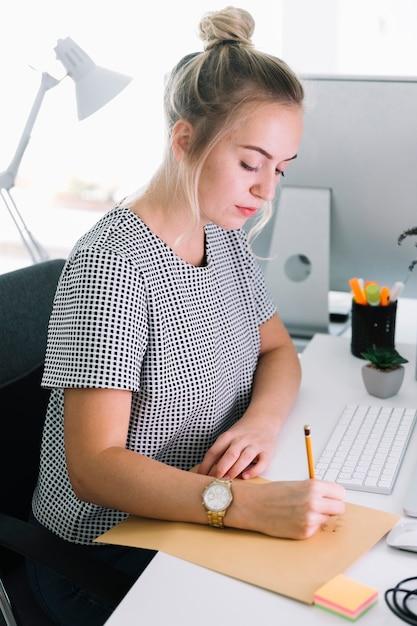 Boczny Widok Bizneswomanu Writing Na Brown Papierze Nad Białym Biurkiem Darmowe Zdjęcia