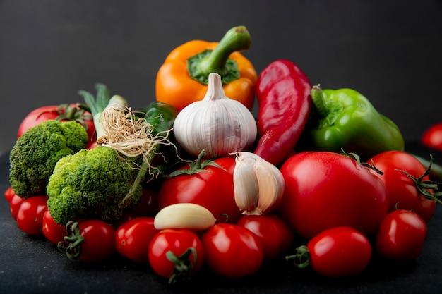 Boczny Widok Dojrzałych świeżych Warzyw Kolorowych Dzwonkowych Pieprzy Pomidorów Czosnku Brokuły I Zielona Cebula Na Czarnym Tle Darmowe Zdjęcia