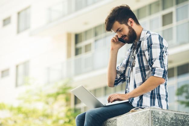 Boczny widok facet odpowiada rozmowę telefonicza w casualwear podczas gdy obliczający na laptopie outdoors Darmowe Zdjęcia