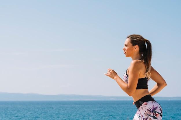 Boczny widok kobieta w sportswear biega blisko morza Darmowe Zdjęcia