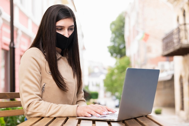 Boczny Widok Kobieta Z Twarzy Maską Pracuje Na Laptopie Outdoors Darmowe Zdjęcia