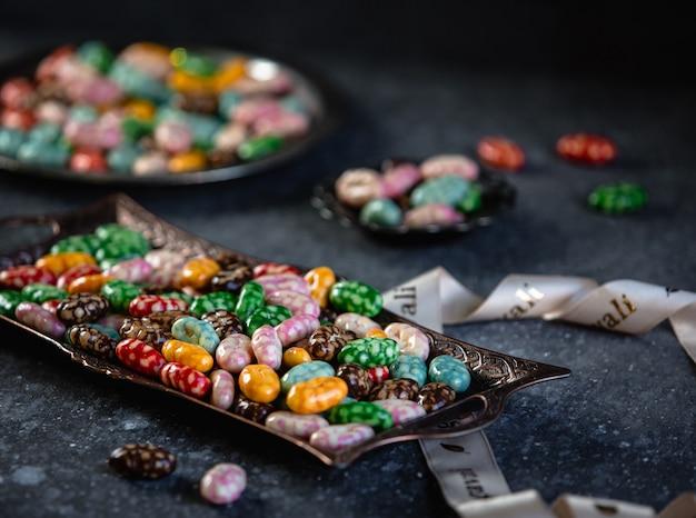 Boczny Widok Kolorowi Oszkleni Cukierki Na Tacy Na Czerń Stole Darmowe Zdjęcia