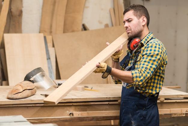 Boczny Widok Męski Cieśla Patrzeje Drewnianą Deskę Darmowe Zdjęcia