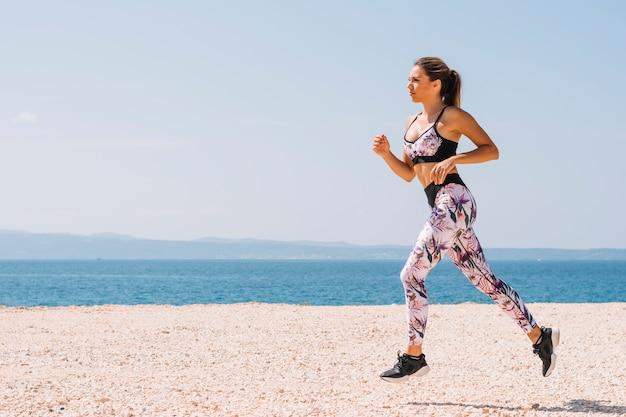 Boczny widok młoda kobieta bieg na plaży Darmowe Zdjęcia