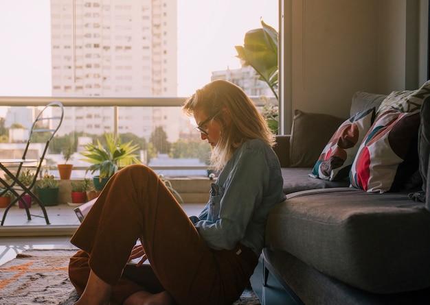 Boczny Widok Młodej Kobiety Obsiadanie Na Dywanowym Używa Laptopie W Domu Darmowe Zdjęcia