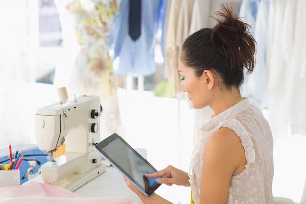 Boczny widok młody żeński projektant mody używa cyfrową pastylkę w studiu Premium Zdjęcia
