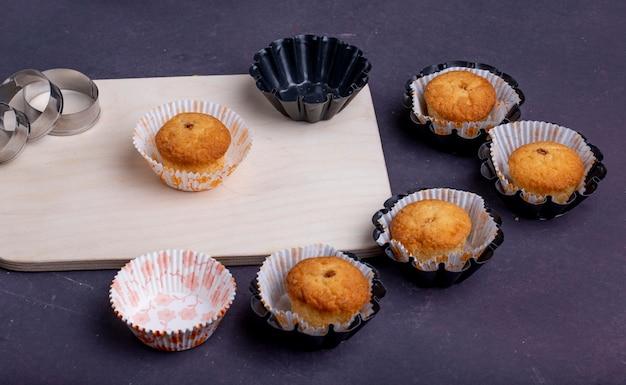 Boczny Widok Muffins W Papierowych Foremkach Na Drewnianej Tnącej Desce I Foremki Do Ciastek Na Wieśniaku Darmowe Zdjęcia