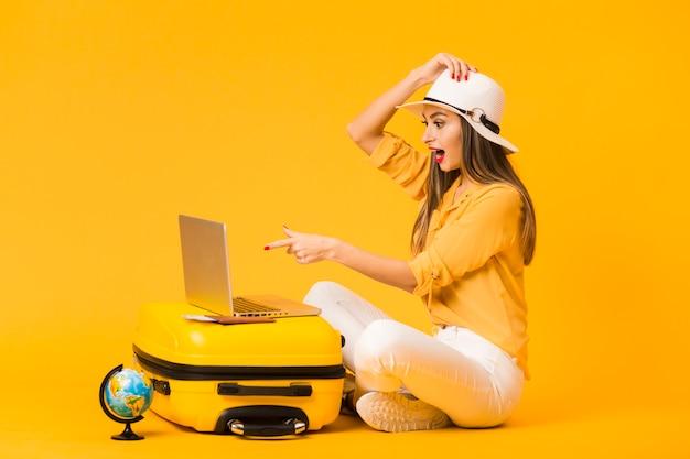 Boczny Widok Patrzeje Laptop Na Górze Bagażu Zdziwiona Kobieta Premium Zdjęcia