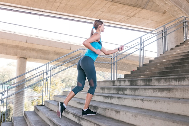 Boczny widok piękna żeńska atleta biega na schody Darmowe Zdjęcia
