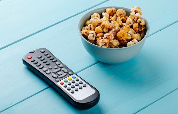Boczny Widok Słodki Karmelu Popkorn W Pucharu I Tv Pilocie Na Błękitnym Tle Darmowe Zdjęcia