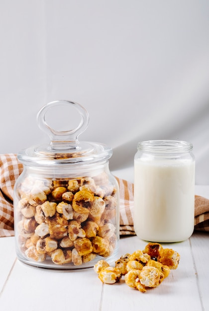 Boczny Widok Słodki Karmelu Popkorn W Szklanym Słoju Na Białym Drewnianym Tle Darmowe Zdjęcia