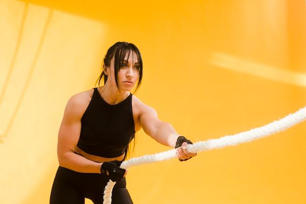 Boczny Widok Sportowa Kobieta W Gym Stroju Ciągnięcia Arkanie Darmowe Zdjęcia