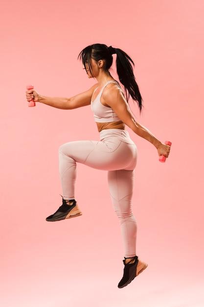 Boczny Widok Sportowy Kobiety Doskakiwanie Z Ciężarami Darmowe Zdjęcia