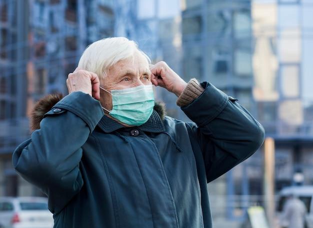 Boczny Widok Starsza Kobieta Jest Ubranym Medyczną Maskę W Mieście Darmowe Zdjęcia