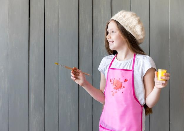 Boczny widok uśmiechniętej dziewczyny mienia żółta farby butelka i paintbrush w ręki pozyci przeciw szarej drewnianej ścianie Darmowe Zdjęcia