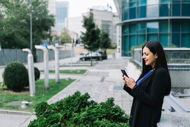 Boczny widok uśmiechnięty bizneswoman używa telefon komórkowego Darmowe Zdjęcia
