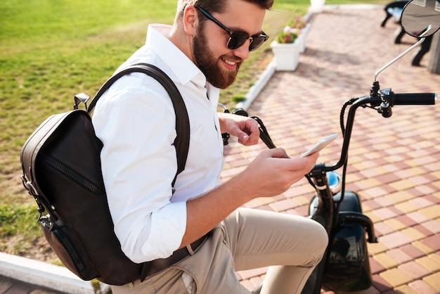 Boczny Widok Uśmiechnięty Brodaty Mężczyzna Siedzi Na Nowożytnym Motocyklu Outdoors I Używa Smartphone W Okularach Przeciwsłonecznych Darmowe Zdjęcia