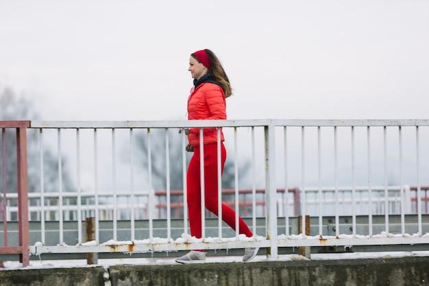 Boczny widok uśmiechnięty młoda kobieta bieg za poręczem w zimie Darmowe Zdjęcia