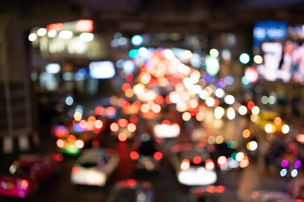 Bokeh świateł z samochodu jest na środku drogi w nocy odblaskowe światło tylne samochodu. Premium Zdjęcia