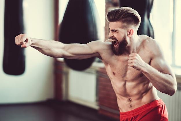 Bokser z nagim torsem ćwiczy ciosy w klubie walki. Premium Zdjęcia