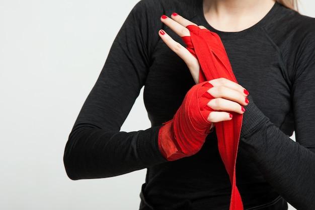 Bokserka Owija Dłonie Czerwonymi Opakowaniami Bokserskimi. Pojedynczo Na Białym Tle Z Miejscem Na Tekst Premium Zdjęcia