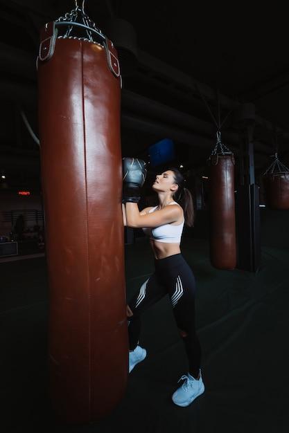 Bokserska Kobieta Pozuje Z Uderzać Pięścią Torbę Na Zmroku. Silna I Niezależna Koncepcja Kobiety Darmowe Zdjęcia