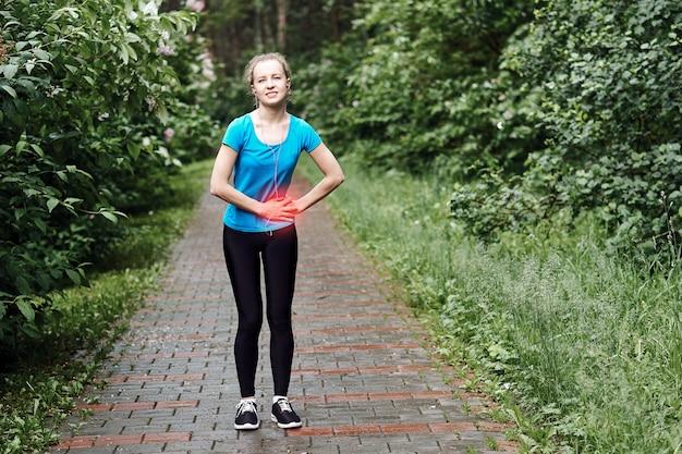 Ból Boczny - Skurcze Boczne U Kobiety Biegacza Po Biegu. Jogging Kobieta Z Bólem Brzucha Po Joggingu Poćwiczyć. Lekkoatletka Premium Zdjęcia