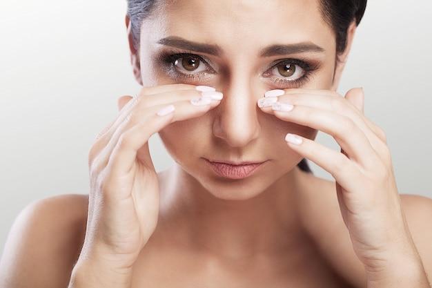 Ból. ból oczu piękna nieszczęśliwa kobieta cierpi na silny ból oka. portret zbliżenie smutny kobiecy stres, dotykając zmęczone bolesne oczy rękami. opieka zdrowotna, pojęcie medyczne. Premium Zdjęcia
