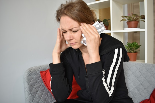 Bół Głowy. Kobieta Z Tabletkami Trzymając Głowę. Objawy Wirusa I Choroby. Premium Zdjęcia
