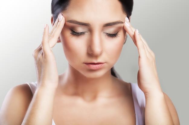 Ból. piękna kobieta, stres i ból głowy z migrenowymi bólami głowy, zmagała się z bólem, dużym portretem Premium Zdjęcia