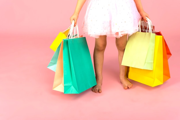 Bose Stopy Dziewczynki I Paczki Z Zakupami W Rękach Małego Zakupoholiczki Na Różowej Pastelowej ścianie. Koncepcja Zakupów Online, Premium Zdjęcia