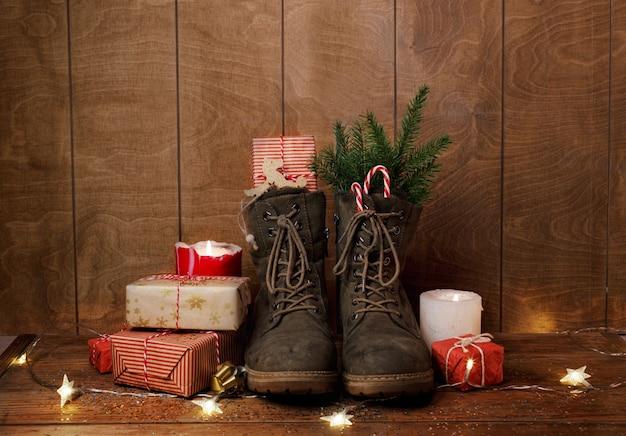 Boże Narodzenie Buty Na Drewnianym Tle Wokół Prezentów, Płonących świec Premium Zdjęcia