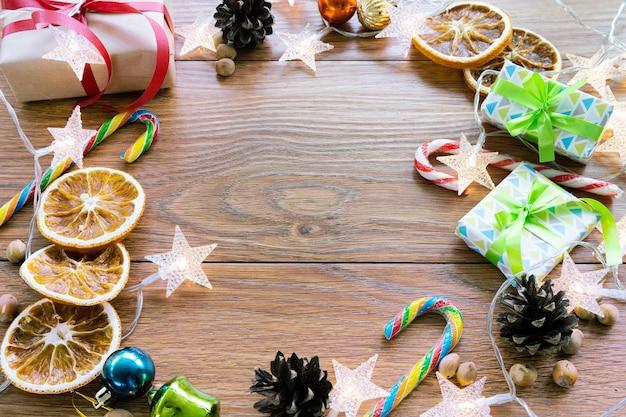 Boże Narodzenie Nowy Rok Ciemne Tło Z Uroczysty Ornament I Pudełka Na Prezenty, Cukierki, Pomarańcza, Szyszki, Zabawki świąteczne. święto Nowego Roku, Pojęcie Obchodów. Premium Zdjęcia