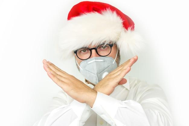 Boże Narodzenie Odwołane Koncepcję, Mężczyzna W Kapeluszu Xmas I Masce Ochronnej Pokazujący Znak Stop Na Rękach Premium Zdjęcia