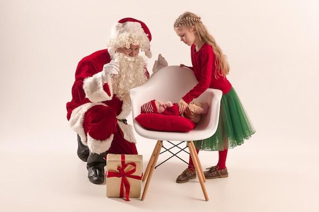 Boże Narodzenie Portret Cute Little Noworodka Dziewczynka, Całkiem Nastoletnia Siostra, Ubrana W Ubrania świąteczne I świętego Mikołaja Z Pudełkiem Darmowe Zdjęcia