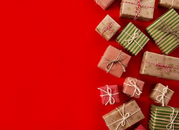 Boże Narodzenie Przedstawia Prezenty Na Czerwonym Tle. Proste, Klasyczne Czerwono-białe Pudełka Na Prezenty Ze Wstążką Premium Zdjęcia