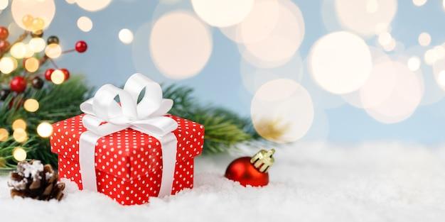Boże Narodzenie Pudełko, Czerwona Piłka Ze Złotymi światłami Na Niebieskim Tle Premium Zdjęcia