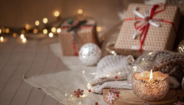Boże Narodzenie Tło Z Srebrnymi Ozdobnymi Płonącymi świecami, światłami I Pudełkami Na Prezenty Na Niewyraźne Tło. Skopiuj Miejsce. Premium Zdjęcia