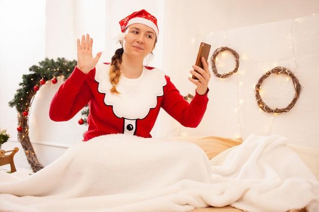 Boże Narodzenie W Internecie Gratulacje Z Okazji Wakacji. Kobieta W Radosnym Kapeluszu Trzyma Telefon I Komunikuje Się Z Przyjaciółmi I Rodziną Za Pomocą Połączenia Wideo Premium Zdjęcia