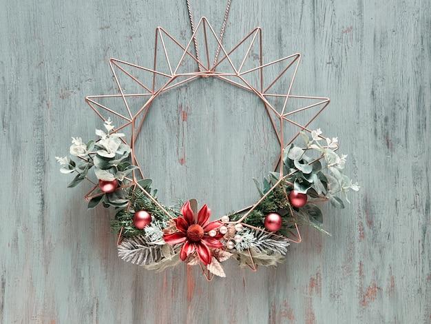 Boże Narodzenie Wieniec Z Zimowych Zielonych Liści I Kwiatów Na Geometrycznej Złotej Metalowej Ramie Na Rustykalne Drewniane Drzwi Premium Zdjęcia