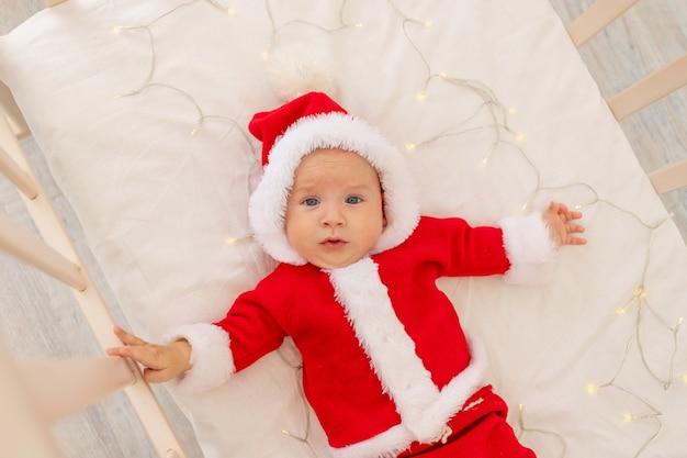 Boże Narodzenie Zdjęcie Dziecka W Stroju Mikołaja Leżącego W łóżeczku W Domu, Widok Z Góry, Szczęśliwego Nowego Roku. Premium Zdjęcia
