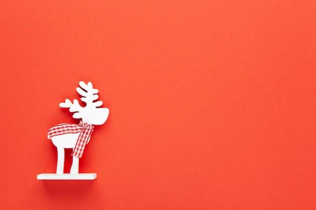 Bożenarodzeniowa dekoracja, zabawkarski biały rogacz ww kratkę szaliku na czerwonym tle z kopii przestrzenią Premium Zdjęcia