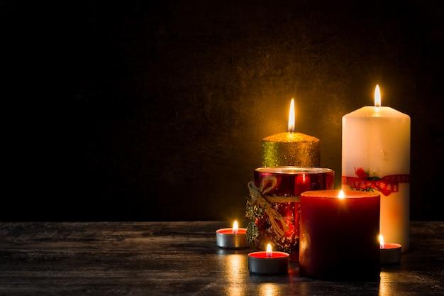 Bożenarodzeniowe świeczki Na Drewnianym Stole. Słabe światło. Premium Zdjęcia