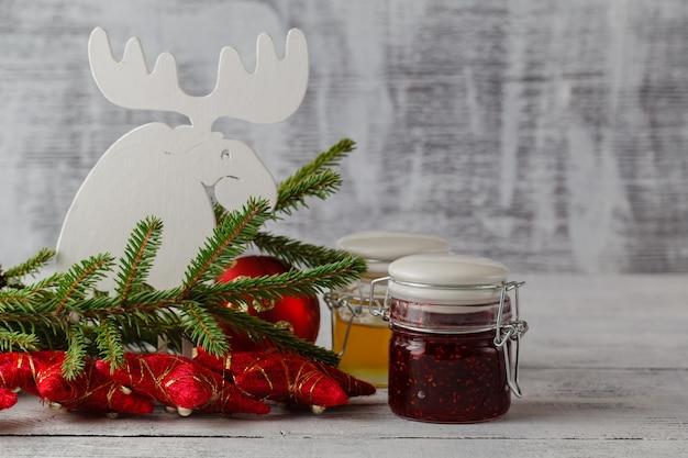 Bożenarodzeniowy Dżemu Słój Z świąteczną Dekoracją Na Białym Drewnianym Stole, Selekcyjna Ostrość. Jadalny Prezent Premium Zdjęcia