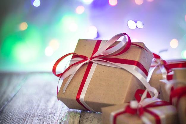 Bożenarodzeniowy prezenta pudełko przeciw bokeh tłu. karta z pozdrowieniami świątecznymi Premium Zdjęcia