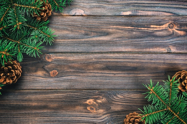 Bożenarodzeniowy rocznik, stonowany szary drewniany tło z jedlinowego drzewa ramą i rożek kopii przestrzeń. widok z góry pusta przestrzeń Premium Zdjęcia