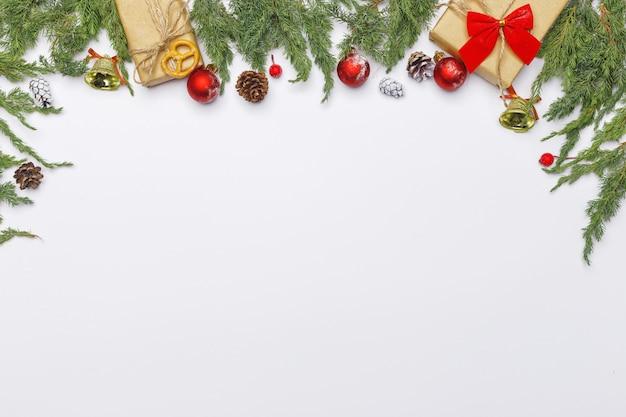 Bożenarodzeniowy skład iglaste gałąź, dekoracje i cukierki na lekkim tle. leżał płasko. widok z góry koncepcja natura nowy rok. skopiuj miejsce Premium Zdjęcia