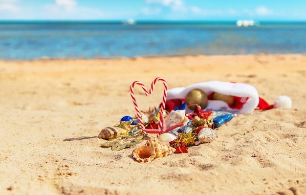 Bożenarodzeniowy tło na plaży z skorupami na piasku. Premium Zdjęcia