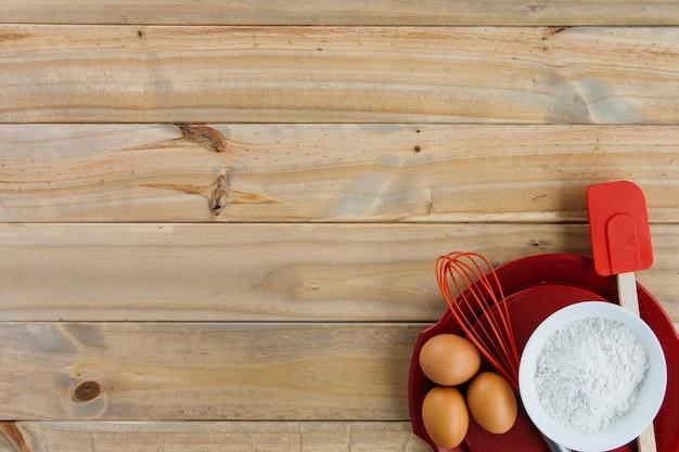 Brązowe jaja; mąka i naczynia na płycie na drewnianym tle Darmowe Zdjęcia
